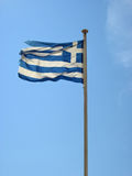 Torn, destroyed the national flag of Greece. Torn, destroyed the national flag of Greece on the blue sky background Royalty Free Stock Photography