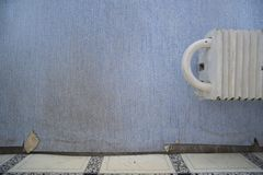 Torn and dirty wallpaper. Next to the radiator, indoor close-up stock images