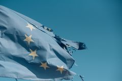 Torn EU flag wave on blue sky. European Union flag with twelve stars on sunny outdoor. Symbol of unity. Euro skepticism. Concept, copy space royalty free stock photography