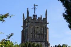 Torn för plant tak för fyrkant kyrkligt med utsmyckat fåfängt för väder ovanför träd mot en blå himmel arkivbild