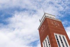Torn för röd tegelsten med klockan på blå himmel och moln Royaltyfri Foto