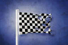 Torn finish flag flying against grunge background.  Stock Photos