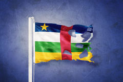 Torn flag of Central African Republic flying against grunge background Royalty Free Stock Photos