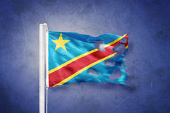 Torn flag of Congo flying against grunge background Royalty Free Stock Image