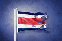 Torn flag of Costa Rica flying against grunge background Stock Photography