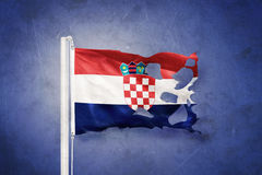 Torn flag of Croatia flying against grunge background Royalty Free Stock Image