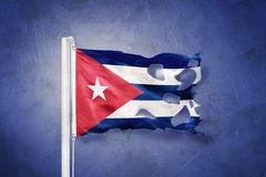 Torn flag of Cuba flying against grunge background Stock Images