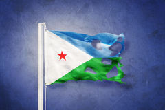 Torn flag of Djibouti flying against grunge background Stock Photography