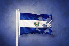 Torn flag of El Salvador flying against grunge background Royalty Free Stock Images