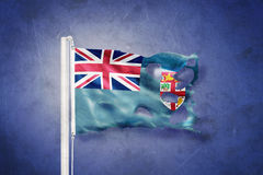 Torn flag of Fiji flying against grunge background Stock Image
