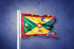 Torn flag of Grenada flying against grunge background Royalty Free Stock Images