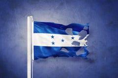 Torn flag of Honduras flying against grunge background Stock Images