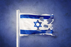 Torn flag of Israel flying against grunge background Royalty Free Stock Photography