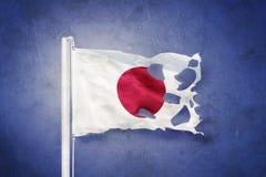 Torn flag of Japan flying against grunge background Royalty Free Stock Image