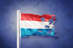 Torn flag of Luxembourg flying against grunge background Stock Photography