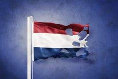 Torn flag of Netherlands flying against grunge background stock illustration