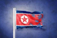 Torn flag of North Korea flying against grunge background Stock Images