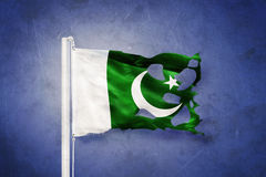 Torn flag of Pakistan flying against grunge background Stock Photos