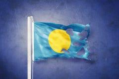 Torn flag of Palau flying against grunge background Stock Image