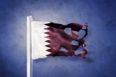 Torn flag of Qatar flying against grunge background Stock Photos