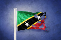 Torn flag of Saint Kitts and Nevis flying against grunge background Stock Photo