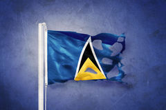 Torn flag of Saint Lucia flying against grunge background Royalty Free Stock Photos
