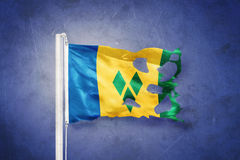 Torn flag of Saint Vincent and the Grenadines flying against grunge background Royalty Free Stock Photo