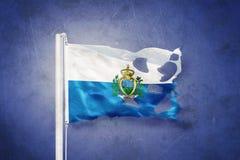 Torn flag of San Marino flying against grunge background Stock Image