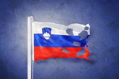 Torn flag of Slovenia flying against grunge background Royalty Free Stock Images
