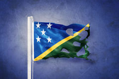 Torn flag of Solomon Islands flying against grunge background Royalty Free Stock Images