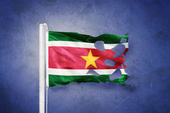 Torn flag of Suriname flying against grunge background Stock Photography