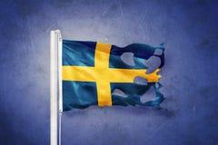 Torn flag of Sweden flying against grunge background Stock Photos