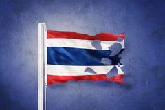 Torn flag of Thailand flying against grunge background Royalty Free Stock Photo