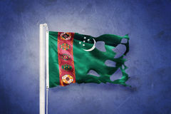Torn flag of Turkmenistan flying against grunge background Stock Photography