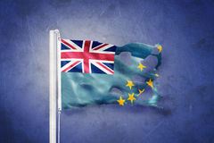 Torn flag of Tuvalu flying against grunge background Royalty Free Stock Photo