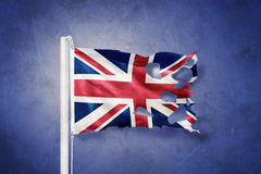 Torn flag of United Kingdom flying against grunge background Stock Photo