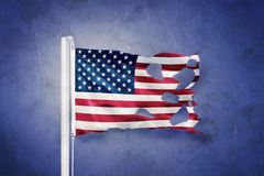 Torn flag of USA flying against grunge background.  Royalty Free Stock Photography