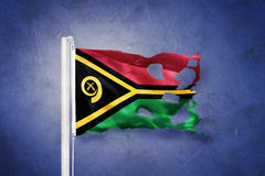 Torn flag of Vanuatu flying against grunge background Royalty Free Stock Photography