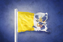Torn flag of Vatican City flying against grunge background.  Stock Photo