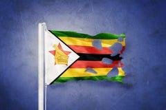 Torn flag of Zimbabwe flying against grunge background Royalty Free Stock Photo
