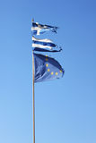Torn Greek flag and torn European Union flag on blue background Royalty Free Stock Image
