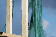 Torn green building mesh on an unguarded unfinished abandoned building. Stock Photo