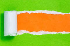 Torn green color paper on orange background Stock Images