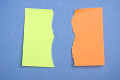 Torn green and orange postits. Post it notes torn. Concept for difference or disagreement or anger Royalty Free Stock Photography