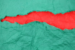 Torn green paper with red paper inside Royalty Free Stock Photography