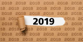 Torn green paper revealing the number 2019 stock photos