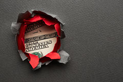 Hole in paper with dollars Royalty Free Stock Image