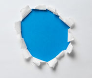 Torn hole on the paper with blue background Stock Images
