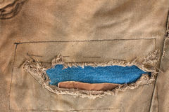 Torn jean. Torn old brown jeans background,dirty pants stock photo