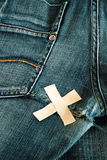 Torn jeans. Torn blue jeans with glued cross strapping tape royalty free stock image